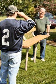 Brad Scherer, left, and Tony Doyle move a bench into place outside Sanatoga Chapel on East High Street.