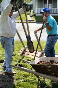 John Scherer, left, and David Updegrove dig holes to secure new benches at the Lower Pottsgrove veterans' memorial.