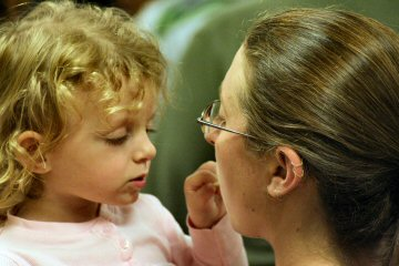 The handle of a lollipop in Mom's mouth fascinates her daughter during an event Wednesday night in Pottstown.