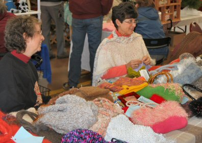 Sandi Gill, left, and Sue Suzenski at their knitting booth last week inside the Sanatoga Fire Company garage.