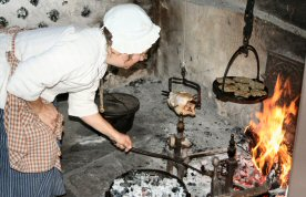 Ruth Konrad of Bally stokes a fire in the kitchen of the Peter Wentz Farmstead.