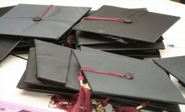 Black graduation caps with maroon tassles await Montgomery County's latest GED graduates Wednesday night.