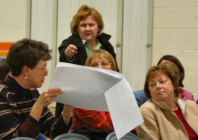 Teachers in the audience during Tuesday's school board meeting examine layout drawings for proposed renovations at Rining Rocks Elementary School.