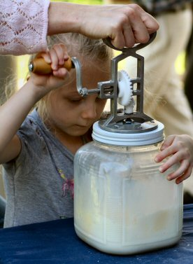 Young Maddy Bocchinfuso churns butter in a jar.