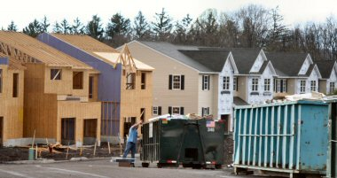 A man disposes of boxes Wednesday at dumpsters within TH Properties' Coddington View community in Upper Pottsgrove (PA) Township. Partially constructed, unfinished homes sit exposed to the elements in the background.