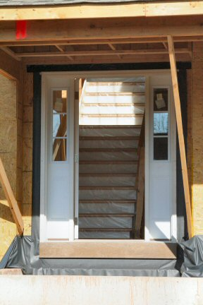 Plastic sheeting protects a finished stairway at 342 Canyon Creek Rd., Gilbertsville, from the elements, even though the doorway and some windows are wide open.