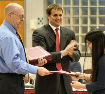Pottsgrove High School student Linda Numagami receives certificates of recognition for her accomplishments in music Tuesday from school board President Michael Neiffer, left, and high school Principal Christopher Shaffer.