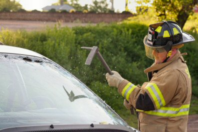 FRagments of glass fly as a Sanatoga fireman practices removing a car windshield.