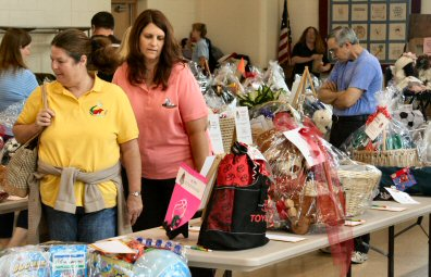Bidders examine gift baskets Saturday at the St. James Church festival.