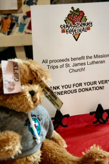 A teddy bear accompanies a tabletop announcement of how festival proceeds would be used.