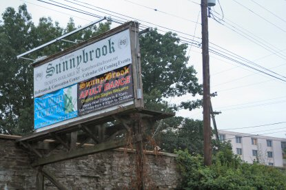 A billboard promoting events at Sunnybrook Ballroom, seen from its parking lot below the East High Street bridge at Sunnybrook Road. Pottstown Memorial Medical Center is in the background at right.